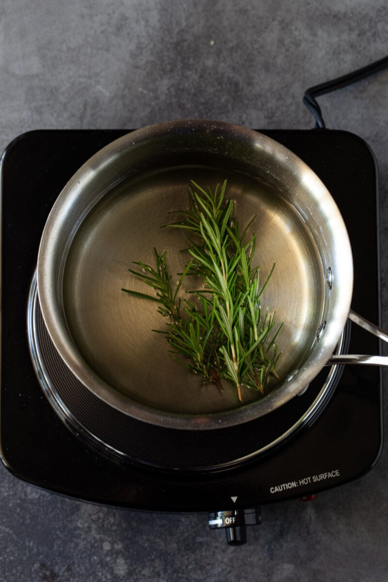 Simple syrup in a stainless steel sauce pan on a black burner with fresh rosemary in pan to be infused.