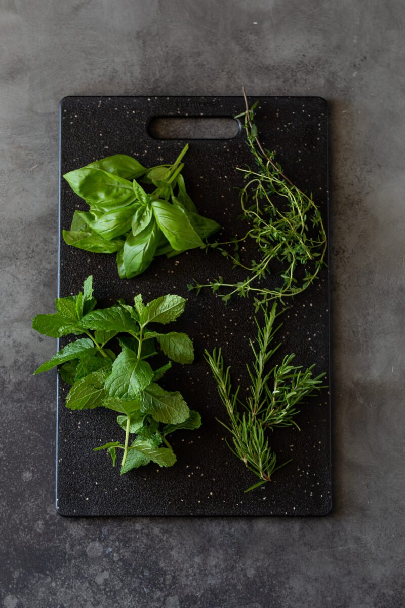 Fresh basil, rosemary, thyme and mint leaves on a black cutting board.