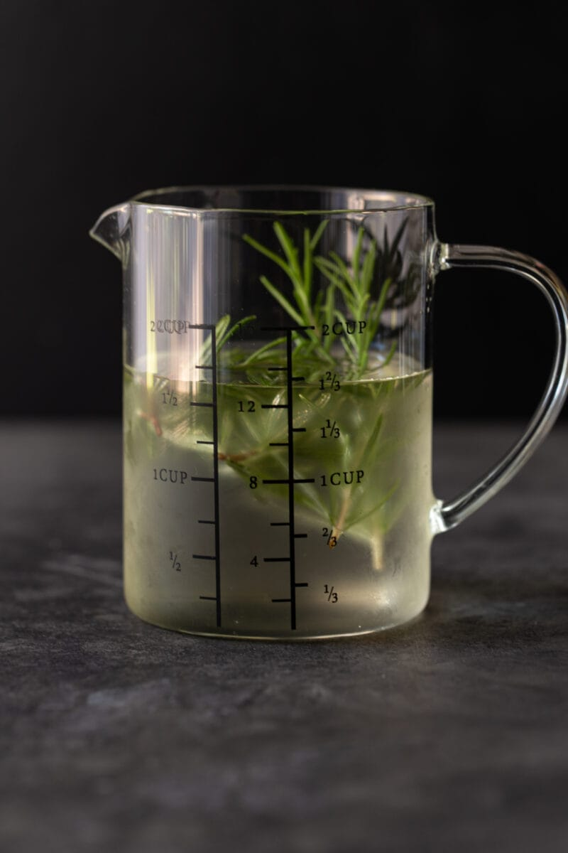 Glass measuring cup filled with simple syrup and fresh rosemary.