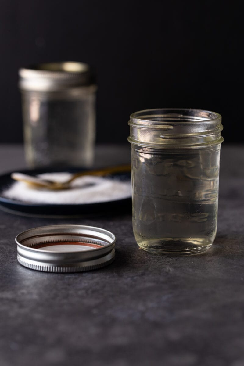2 mason jars filled with simple syrup on a dark background. Lid of mason jar on side for sealing and a dark plate covered with granulated sugar is in the background with a gold spoon for scooping.