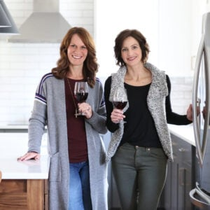 Lisa and Anna holding glasses of wine in test kitchen.