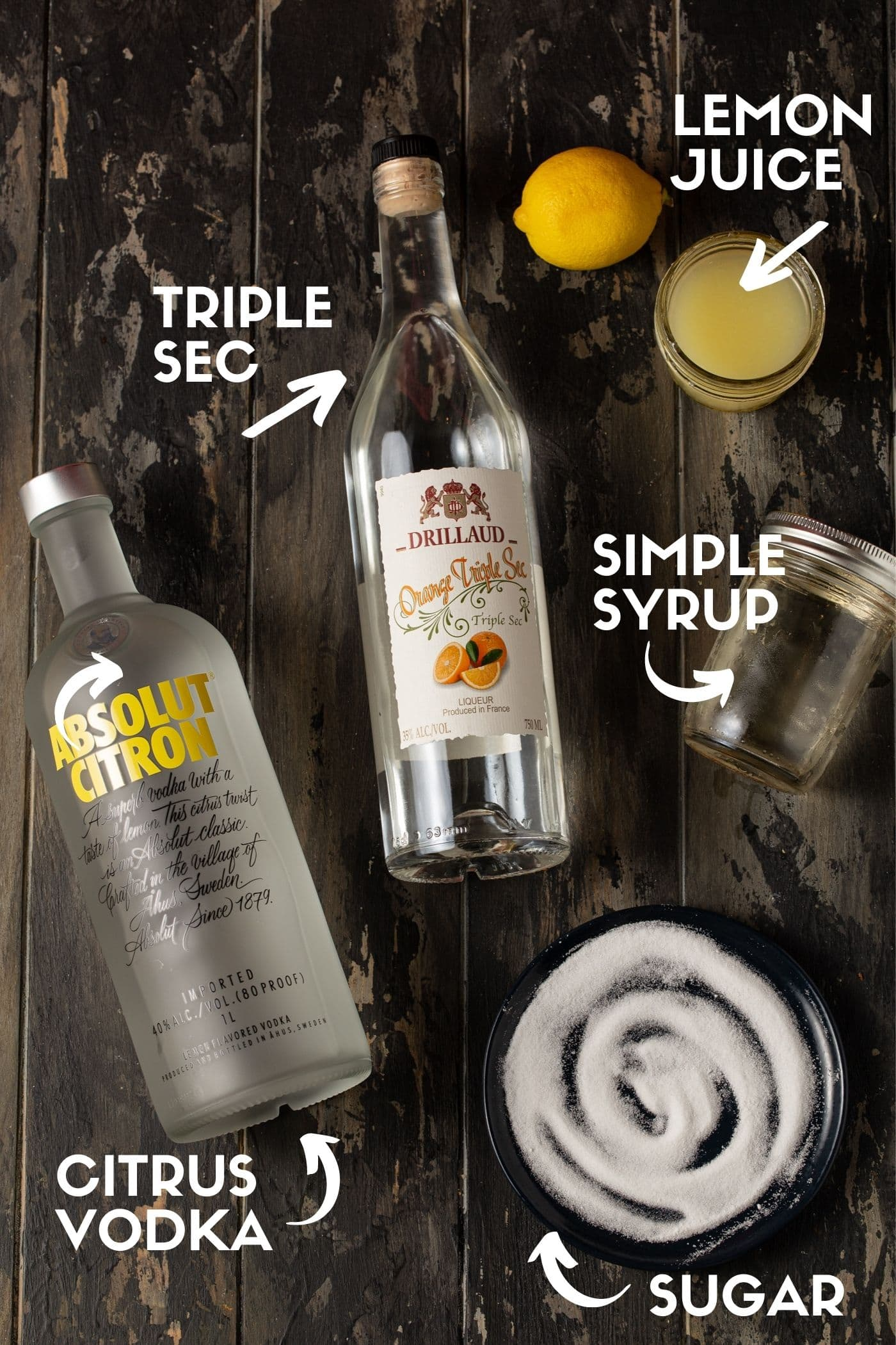 absolut citron vodka bottle, triple sec bottle, small jar filled with lemon juice, mason jar of simple syrup and small black plate topped with superfine sugar on a dark background.