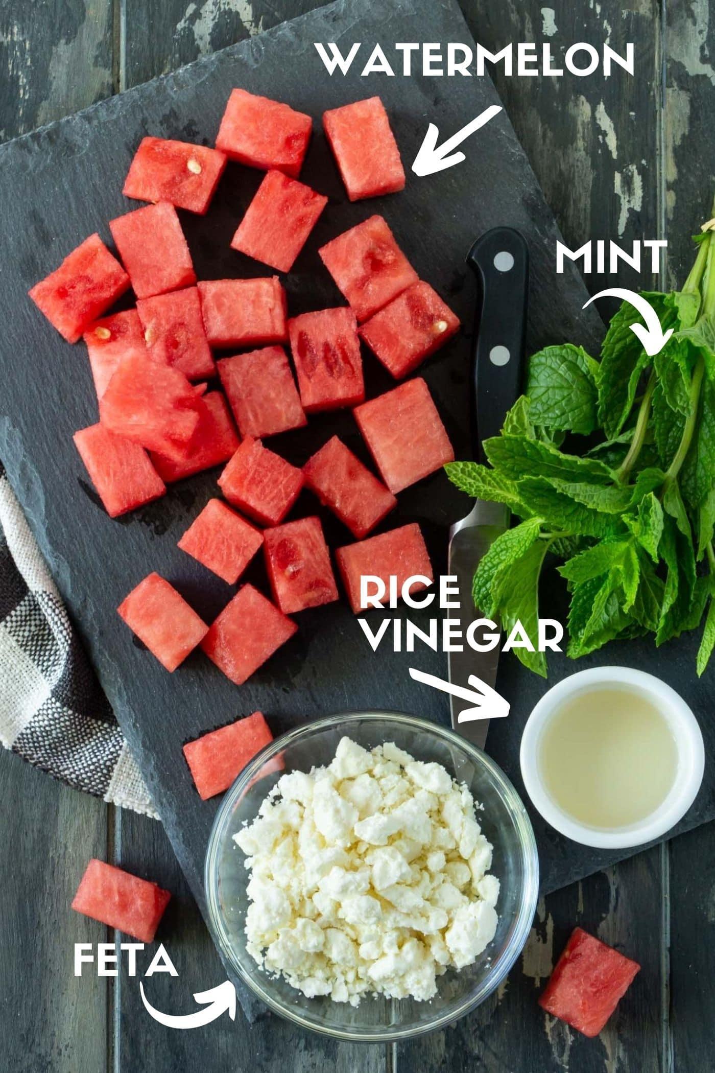 Dark gray cutting board filled with fresh watermelon cubes, salty feta cheese, fresh mint sprigs and rice vinegar.