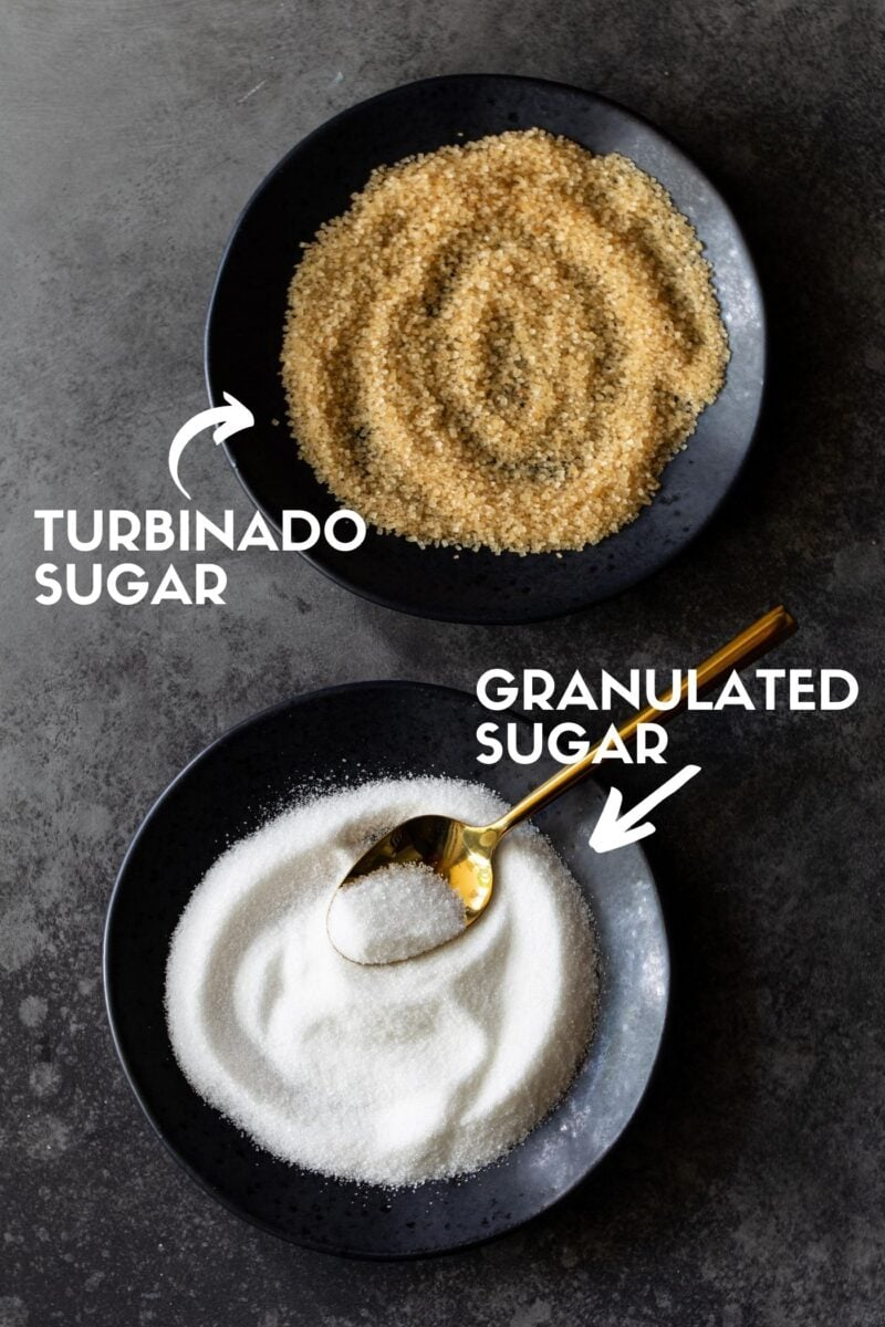 Labeled Raw sugar on a black plate and labeled granulated sugar with a gold spoon for scooping on a dark charcoal background.on a black plate