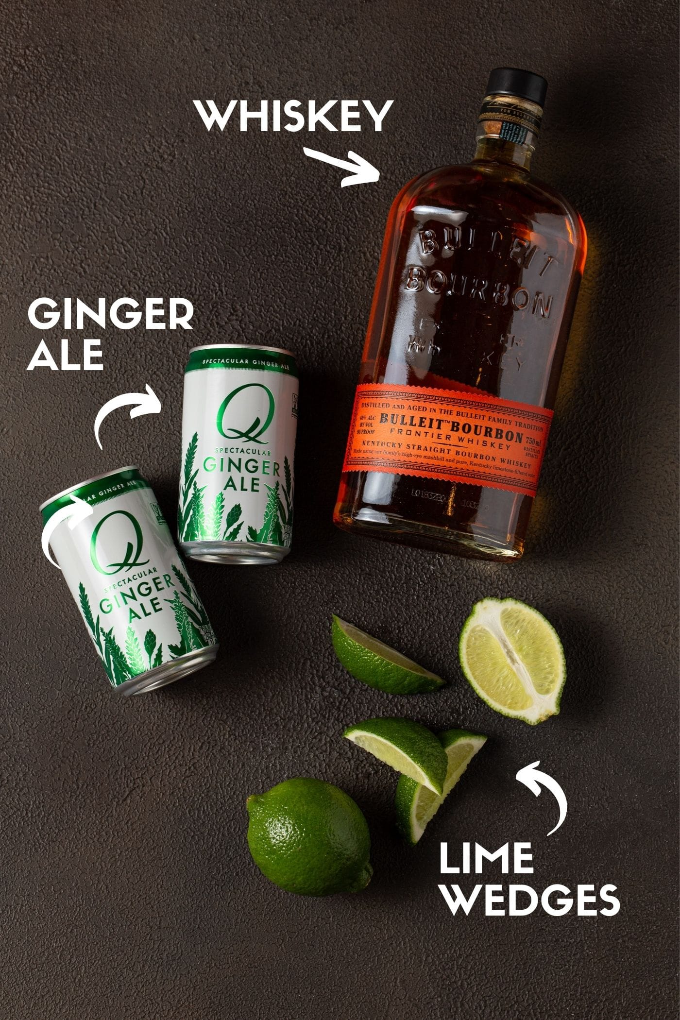 Ingredients for Whiskey Ginger drink, including, whiskey, ginger ale and lime wedges.