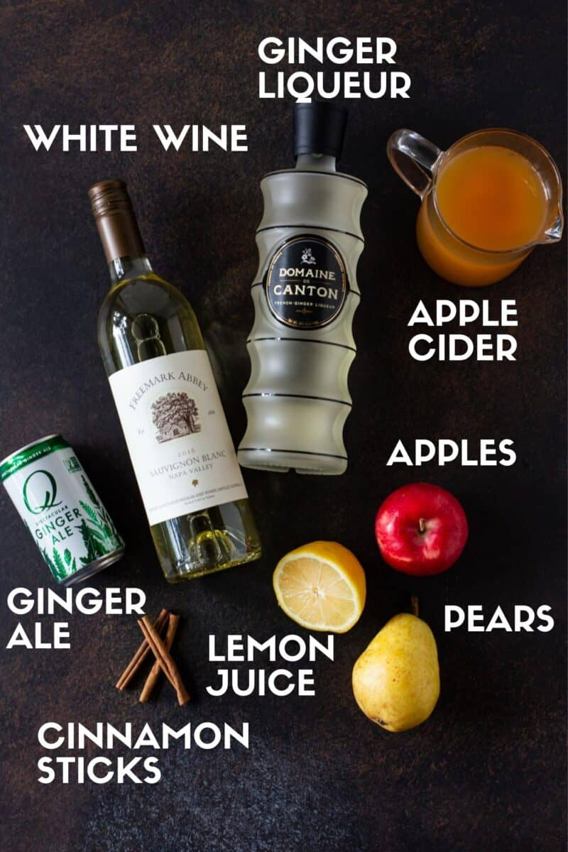 Ingredients for Apple Cider Sangria on a dark board, including apple cider, ginger liquer, apples, pears, lemon juice, white wine and cinnamon sticks.