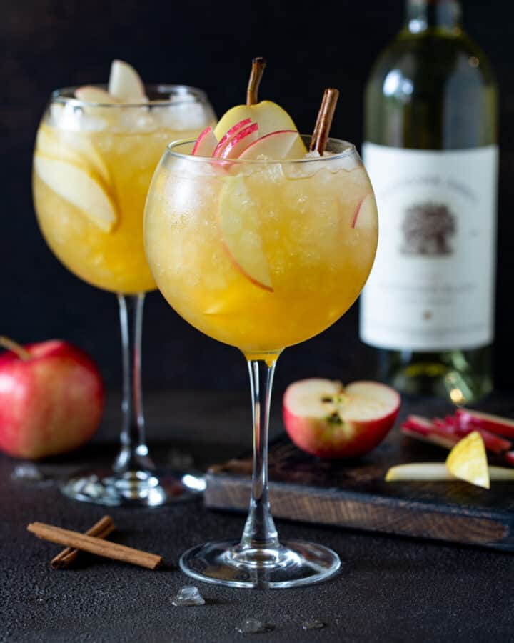 Two balloon wine glasses filled with Apple Cider Sangria. Garnished with fresh apple and pear slices and cinnamon sticks.