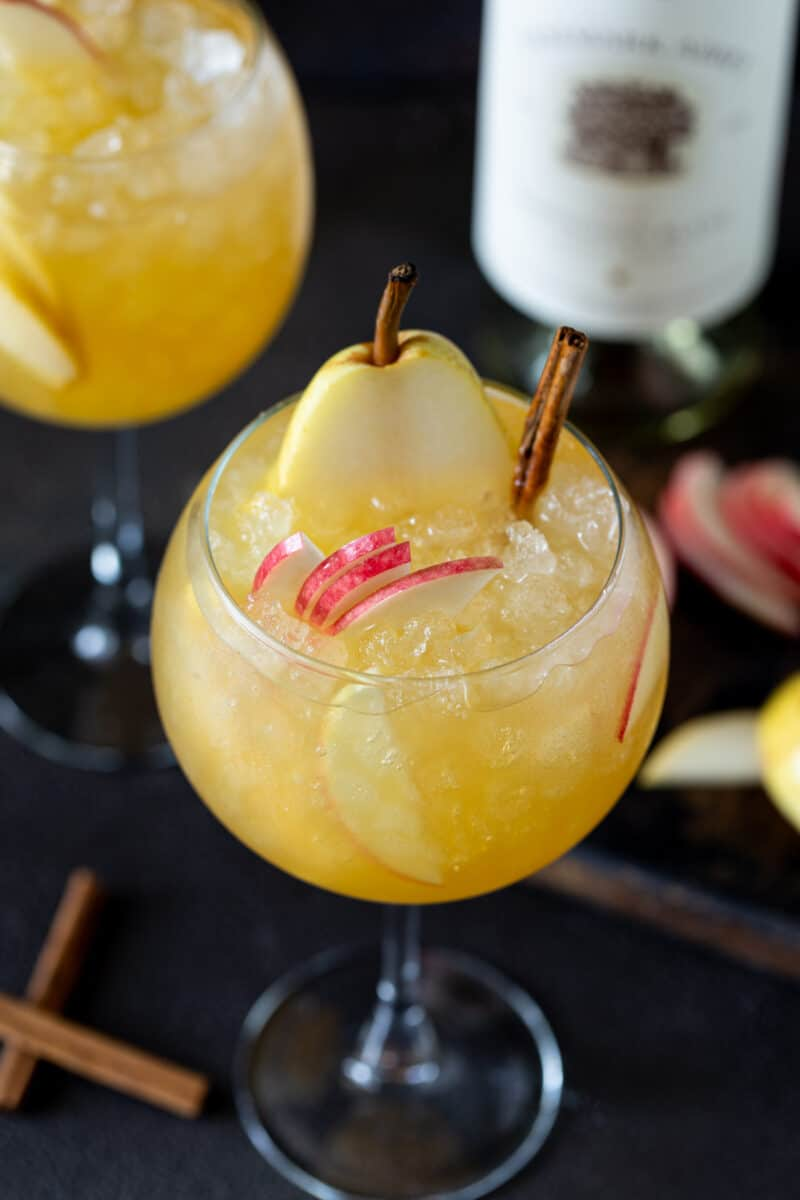 Top down shot of a wine glass filled with Apple Cider Sangria. Glass is garnished with fresh apple and pear slices and cinnamon sticks.