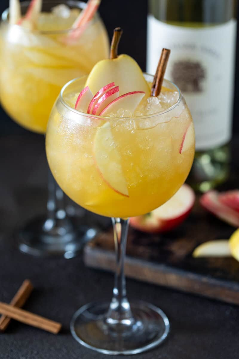 Two balloon wine glasses filled with Apple Cider Sangria. Glasses are garnished with fresh apple and pear slices and cinnamon sticks.