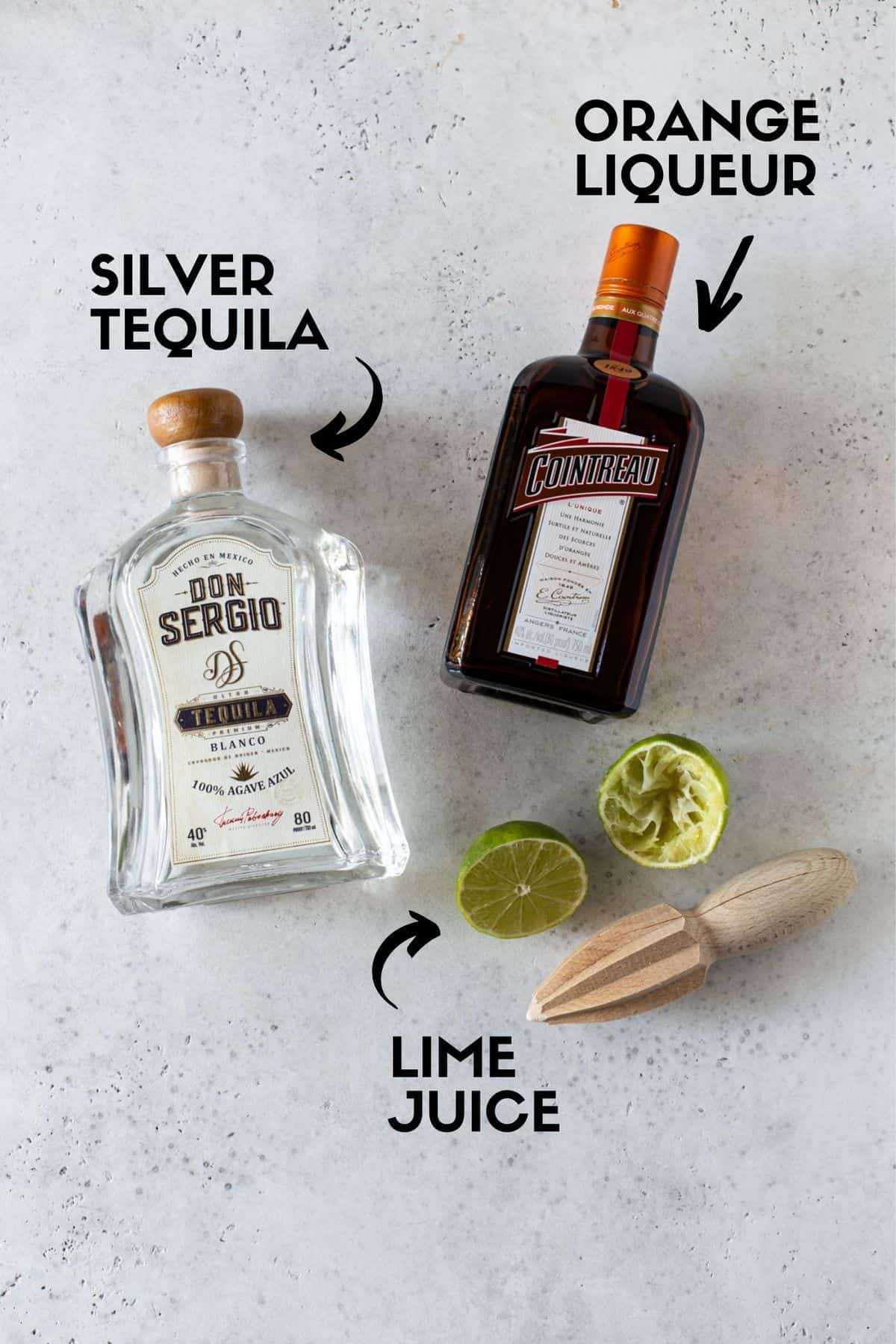 Margarita ingredients including tequila bottle, cointreau bottle and lime half.