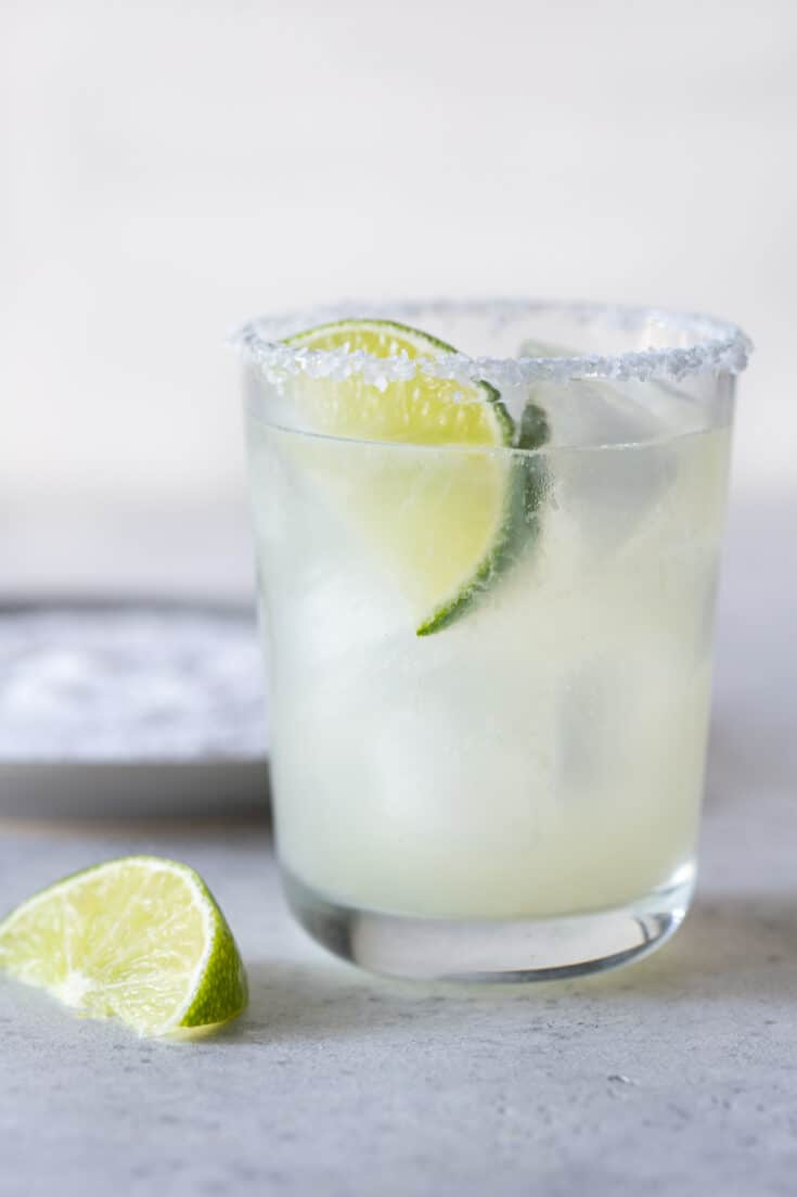 single low ball glass with a salted rim filled with margarita and a lime wedge for garnish