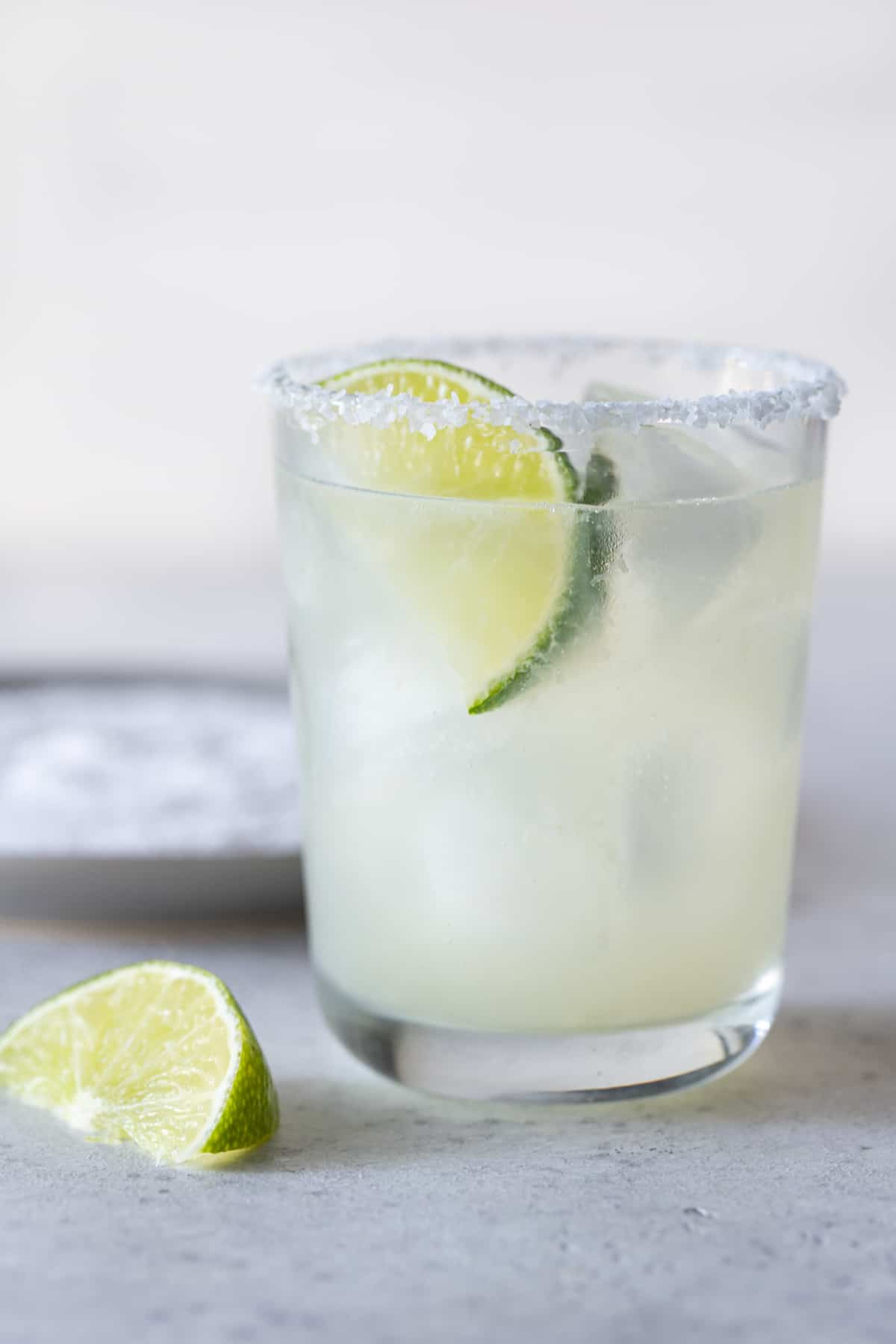 Single low ball glass with a salted rim filled with margarita and a lime wedge for garnish.