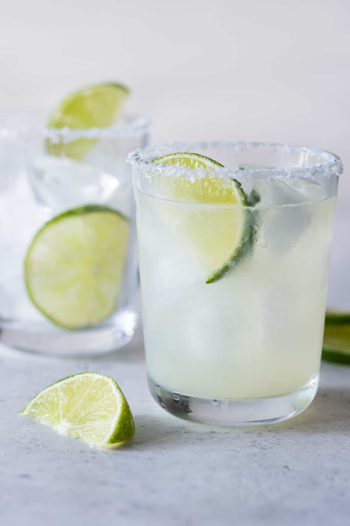 2 low ball glasses filled with ice and margaritas with a salted rim