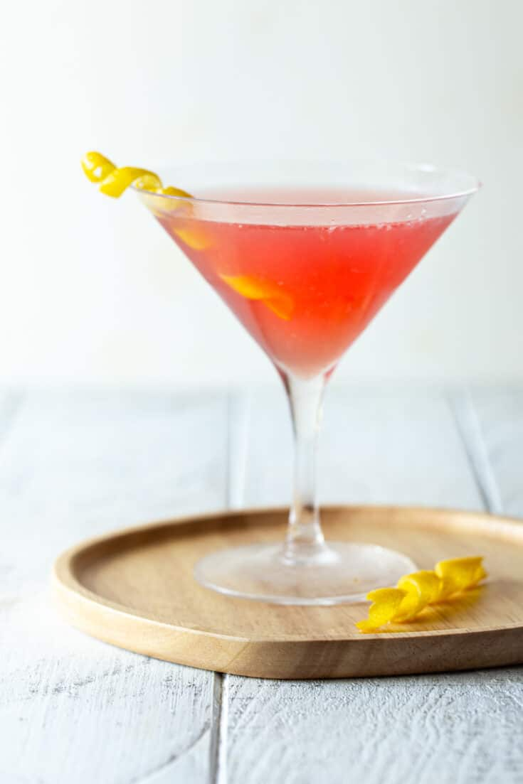 single martini glass filled with pink drink on wooden tray with lemon twist