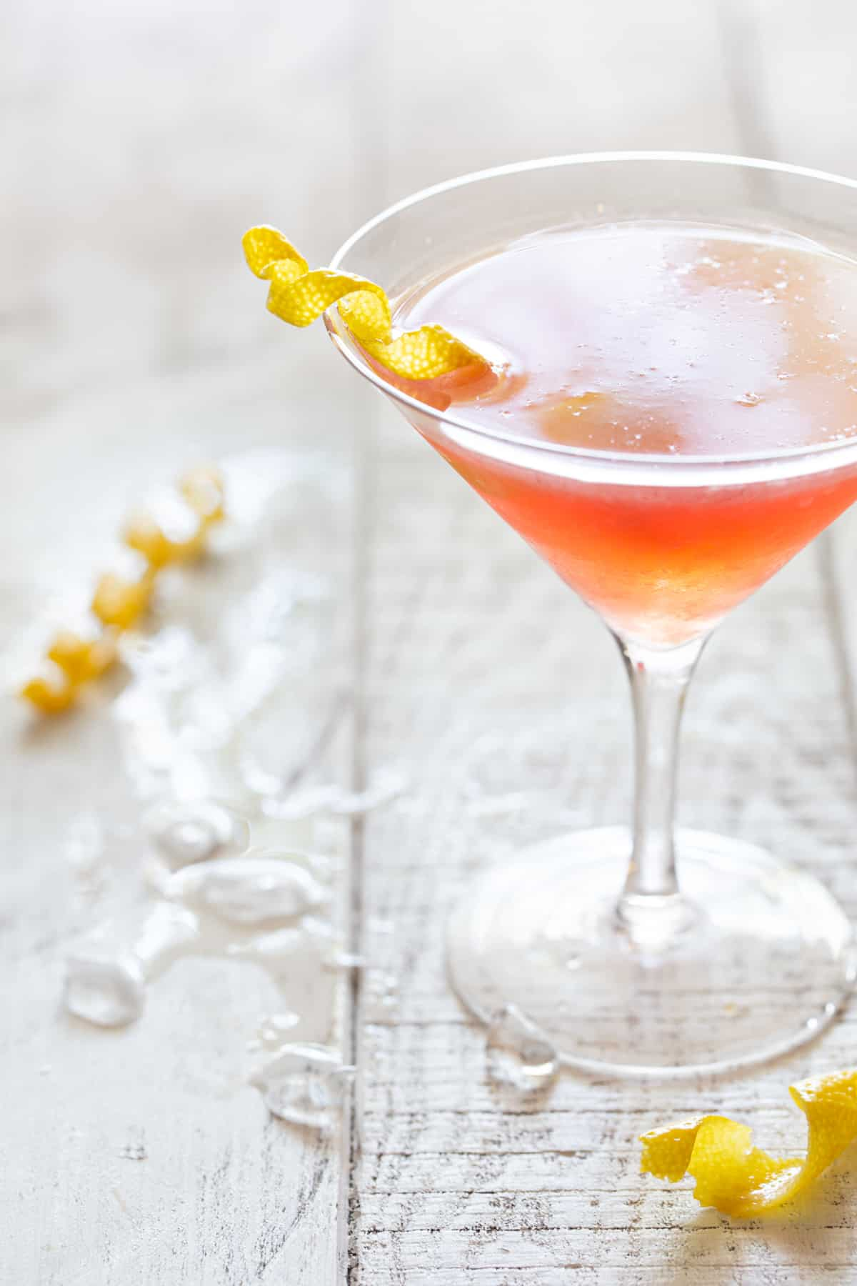 tall martini glass filled with cosmo on a white background with crushed ice and a lemon twist.