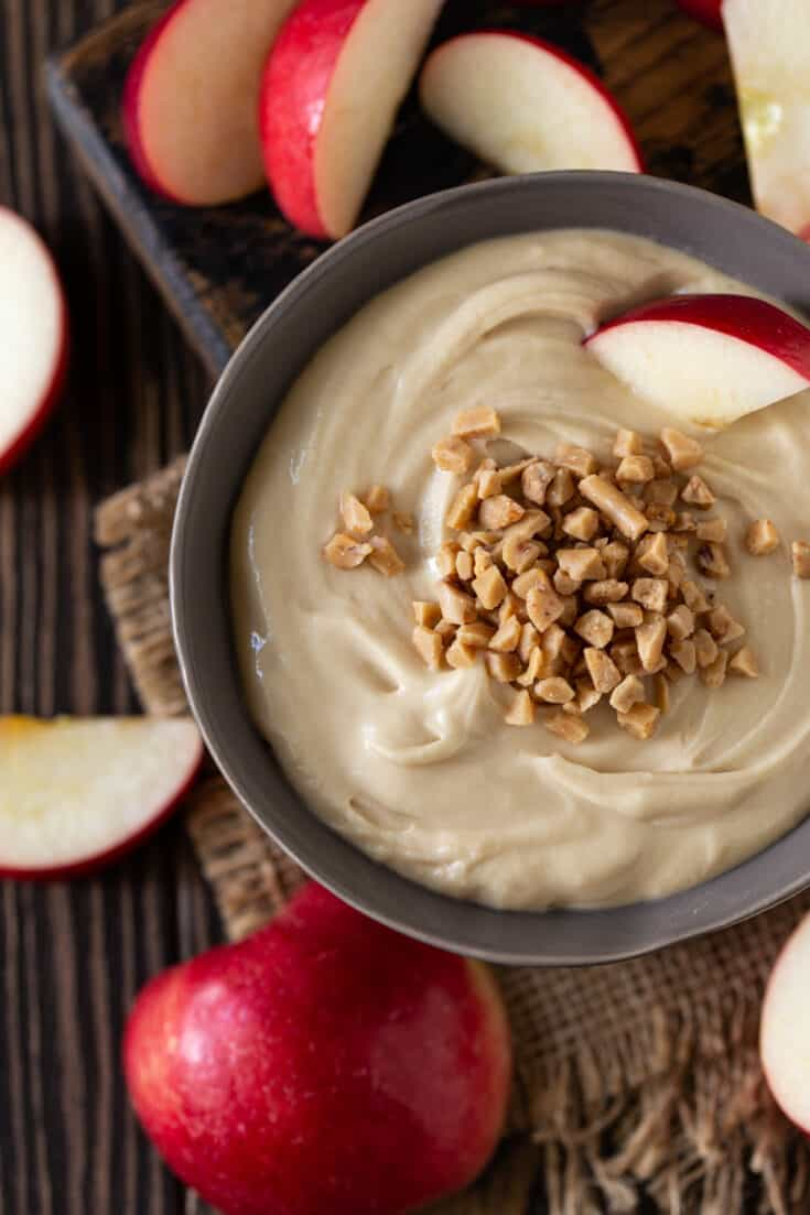 A bowl of food on a plate, with Apple and Cream cheese.