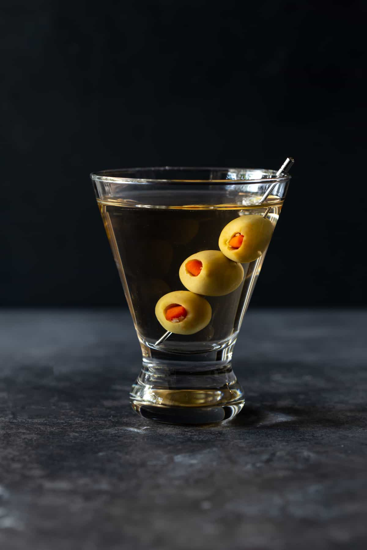 single martini glass filled with gin and olives on a skewer.