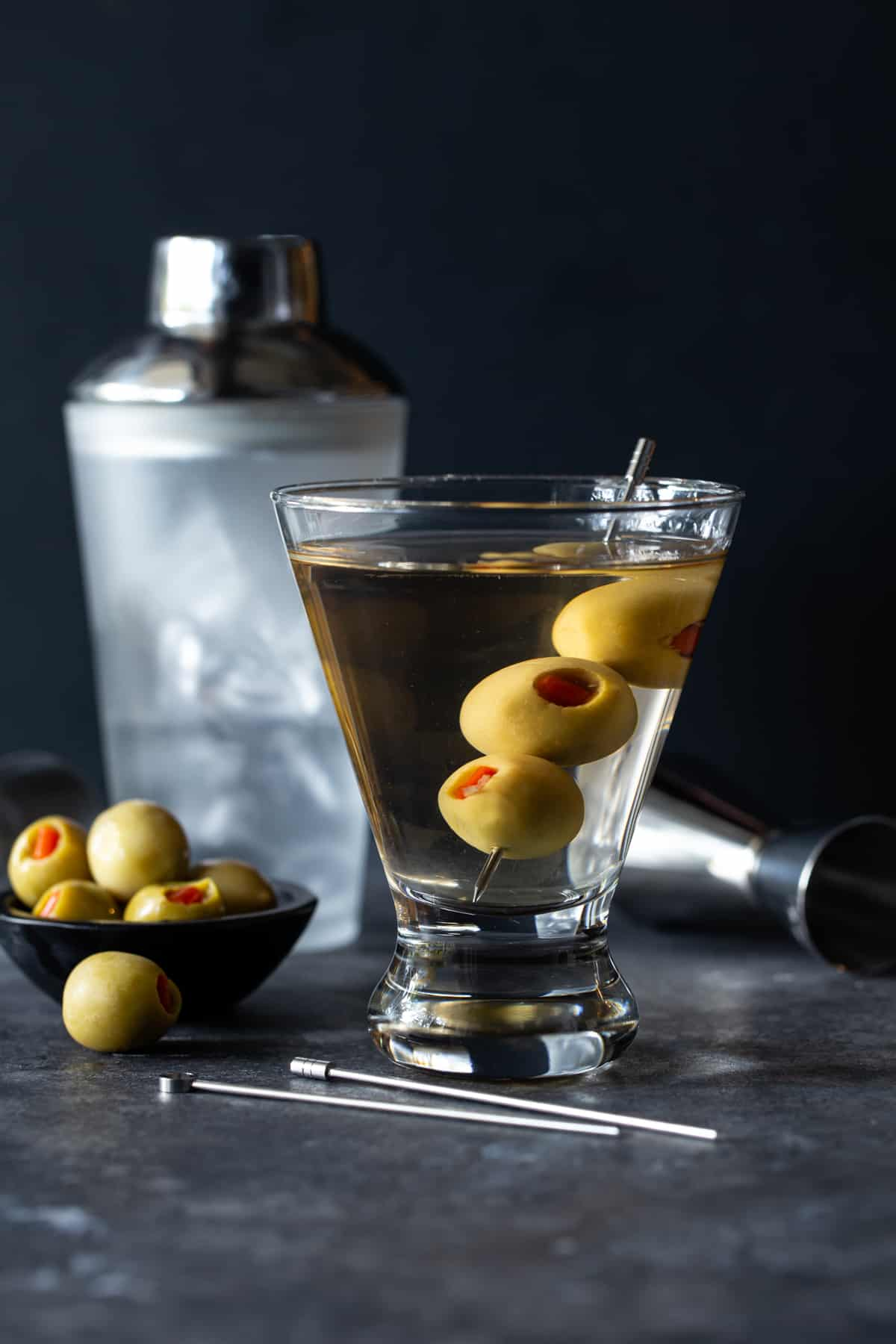 white martini shaker with bowl of olives and full gin martini with jigger.
