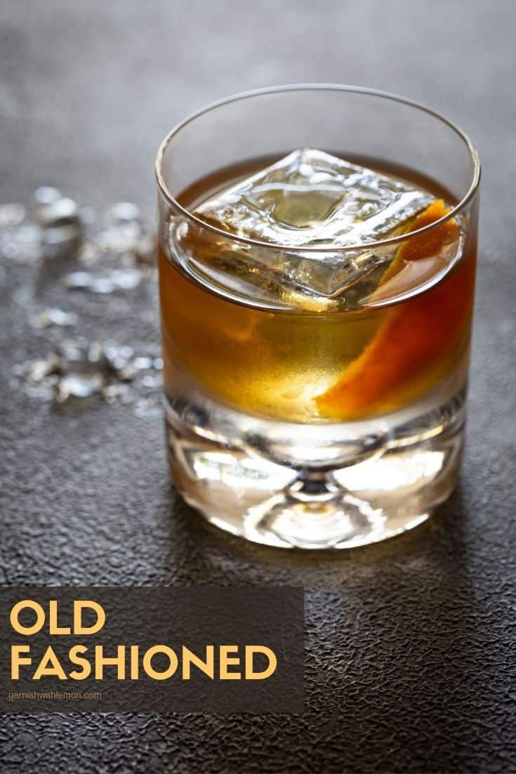 An old fashioned in a lowball glass with a large ice cube and an orange peel