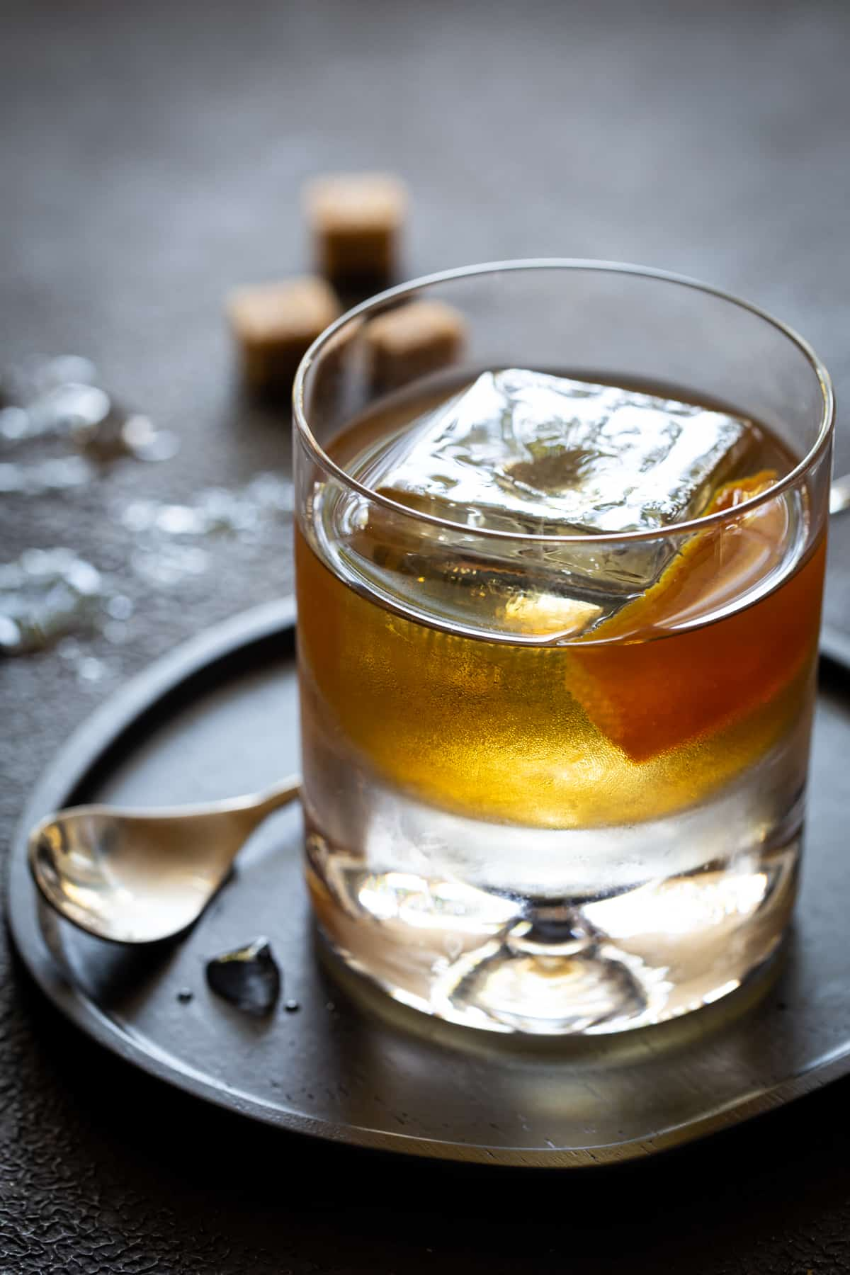 A glass cup on a table, with Old fashioned and Orange