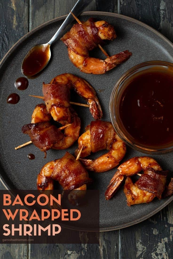 bacon wrapped shrimp on a gray plate with barbecue sauce in a small bowl
