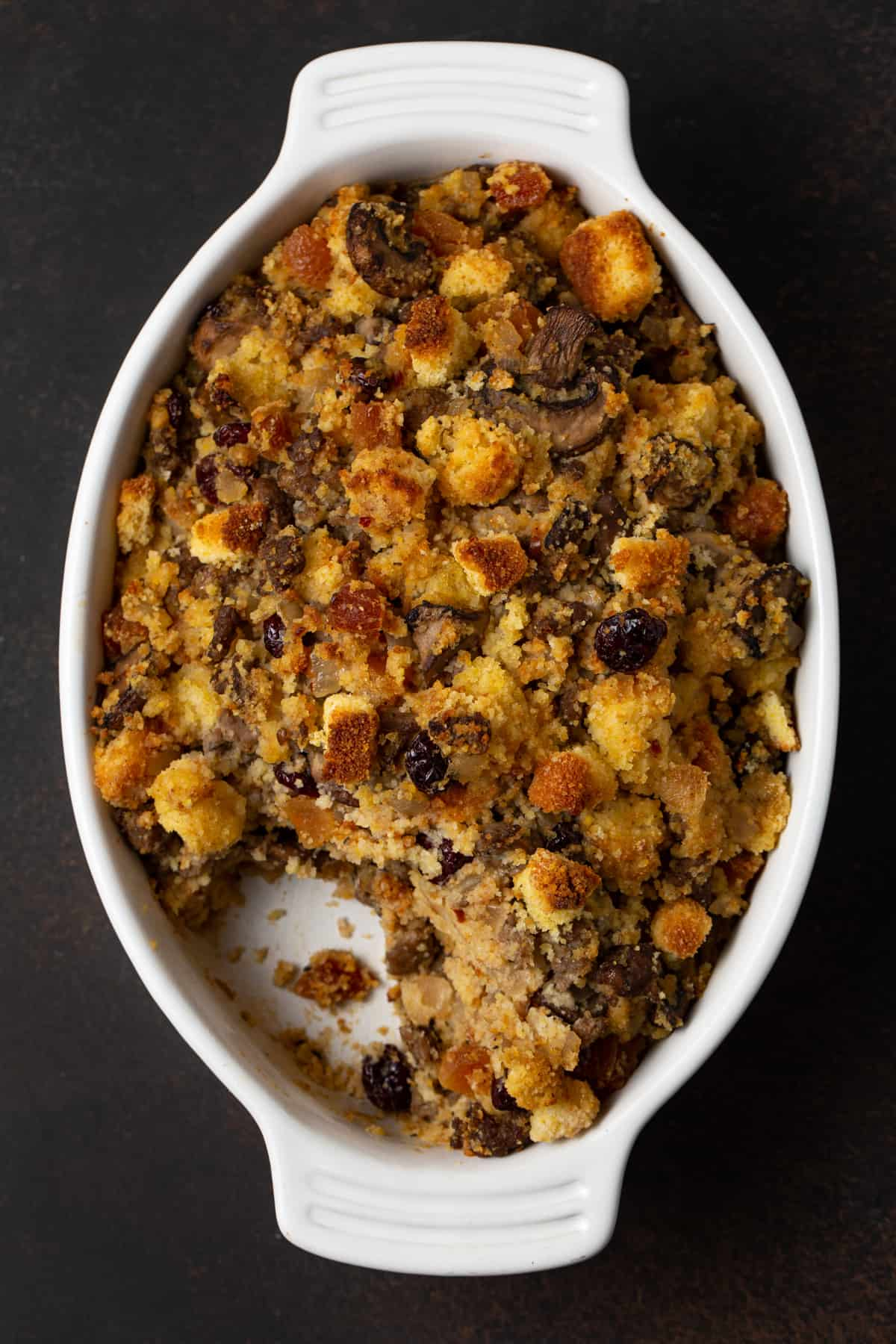 top down shot of white oval casserole dish filled with cornbread sausage stuffing
