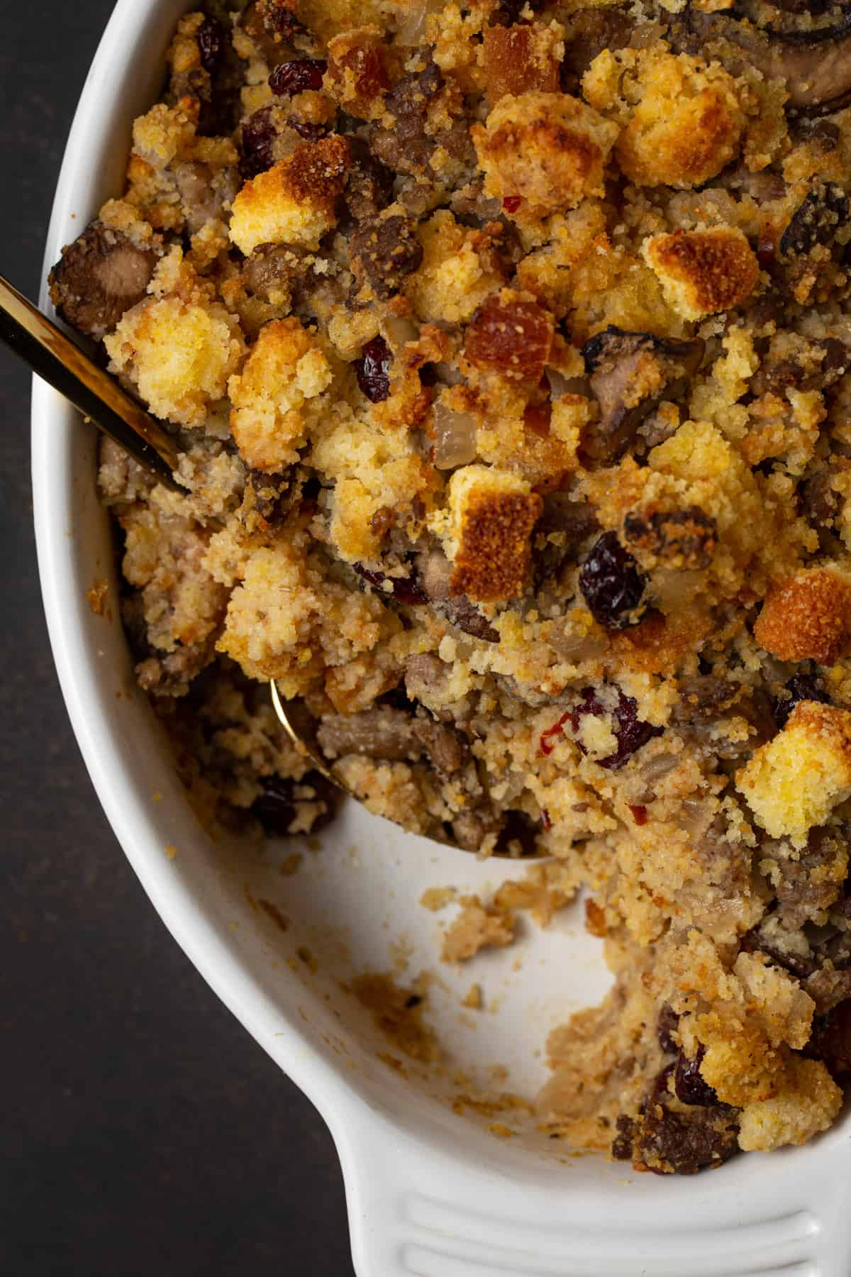 cornbread stuffing in a white baking dish with gold spoon