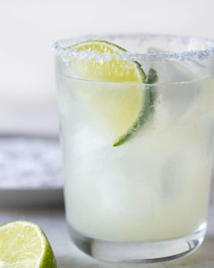 single low ball glass filled with margarita with a salted rim and a lime wedge