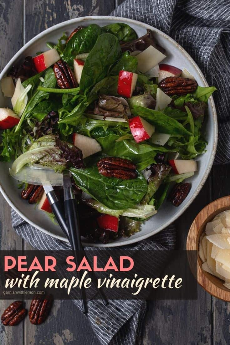 Pear salad in a bowl with candied pecans and shaved Parmesan.
