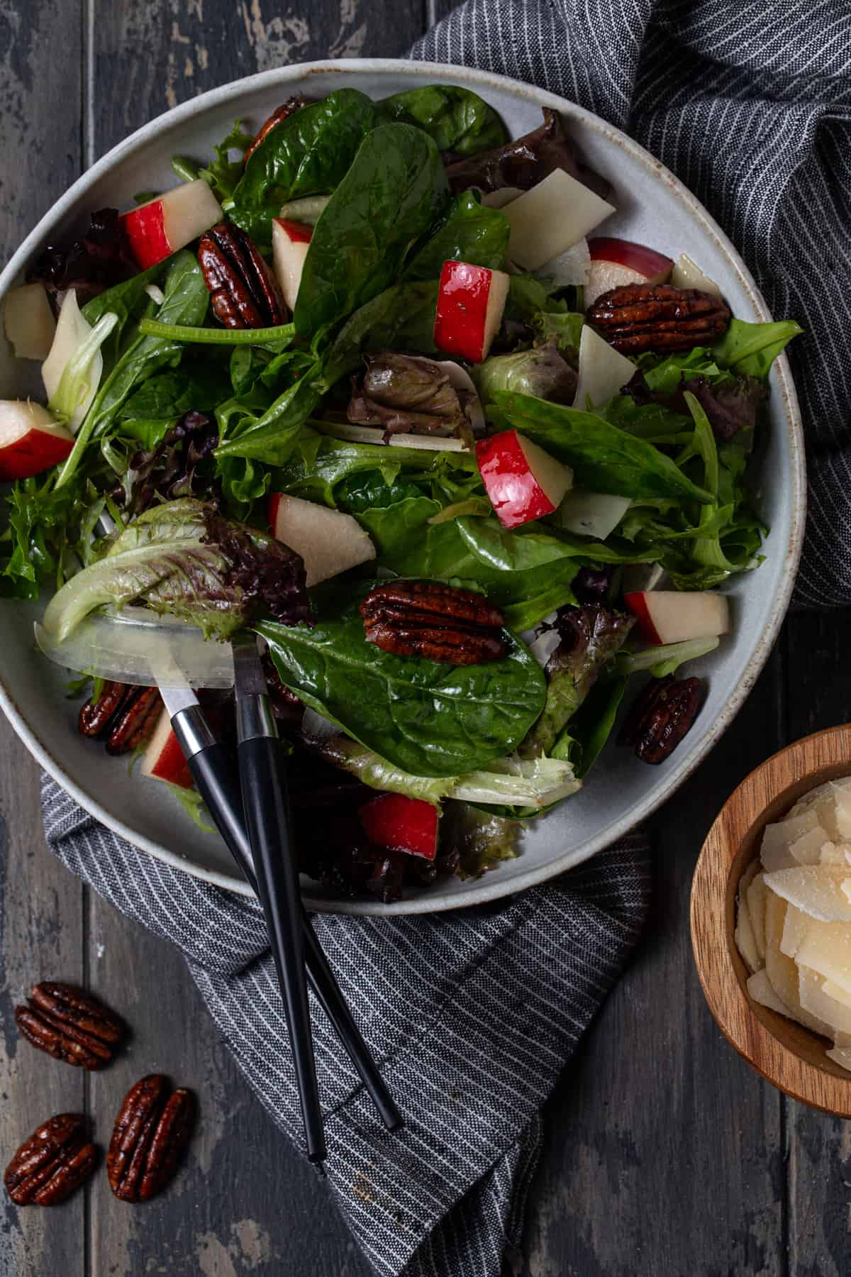 Salad in gray bowl with pears, parmesan cheese and candied pecans.