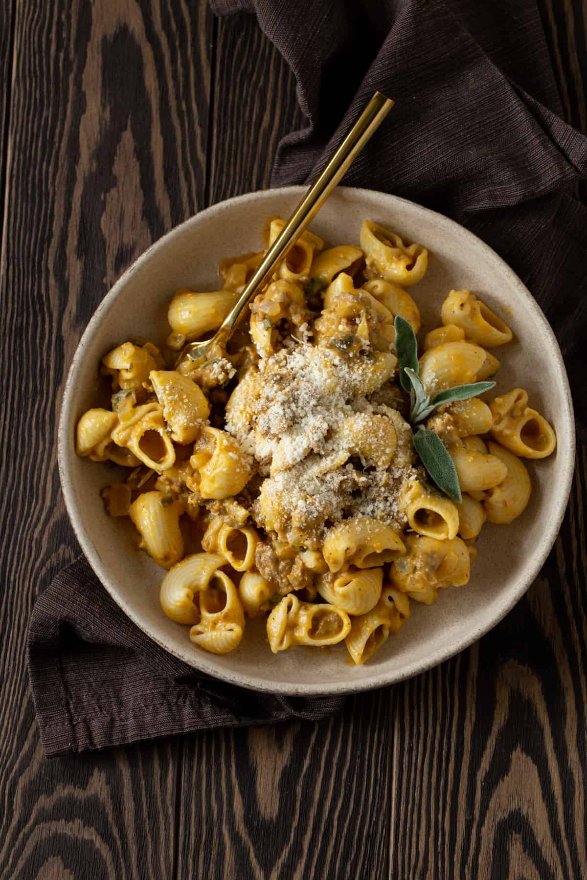 Bowl of pumpkin pasta with sausage, sage and grated parmesan with gold spoon