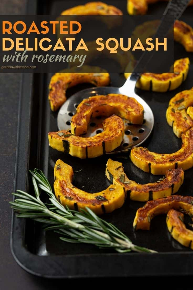 Roasted squash on dark sheet pan with silver lifter and fresh rosemary.