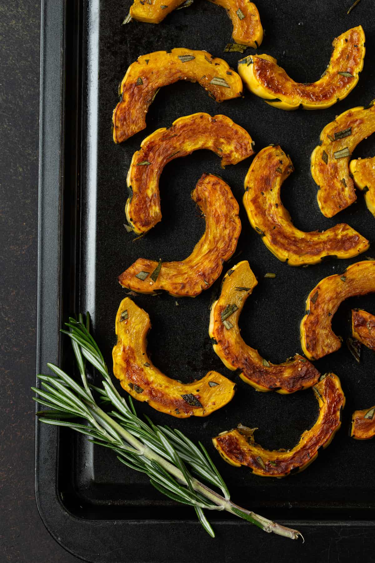 roasted squash pieces on a dark sheet pan with fresh rosemary.
