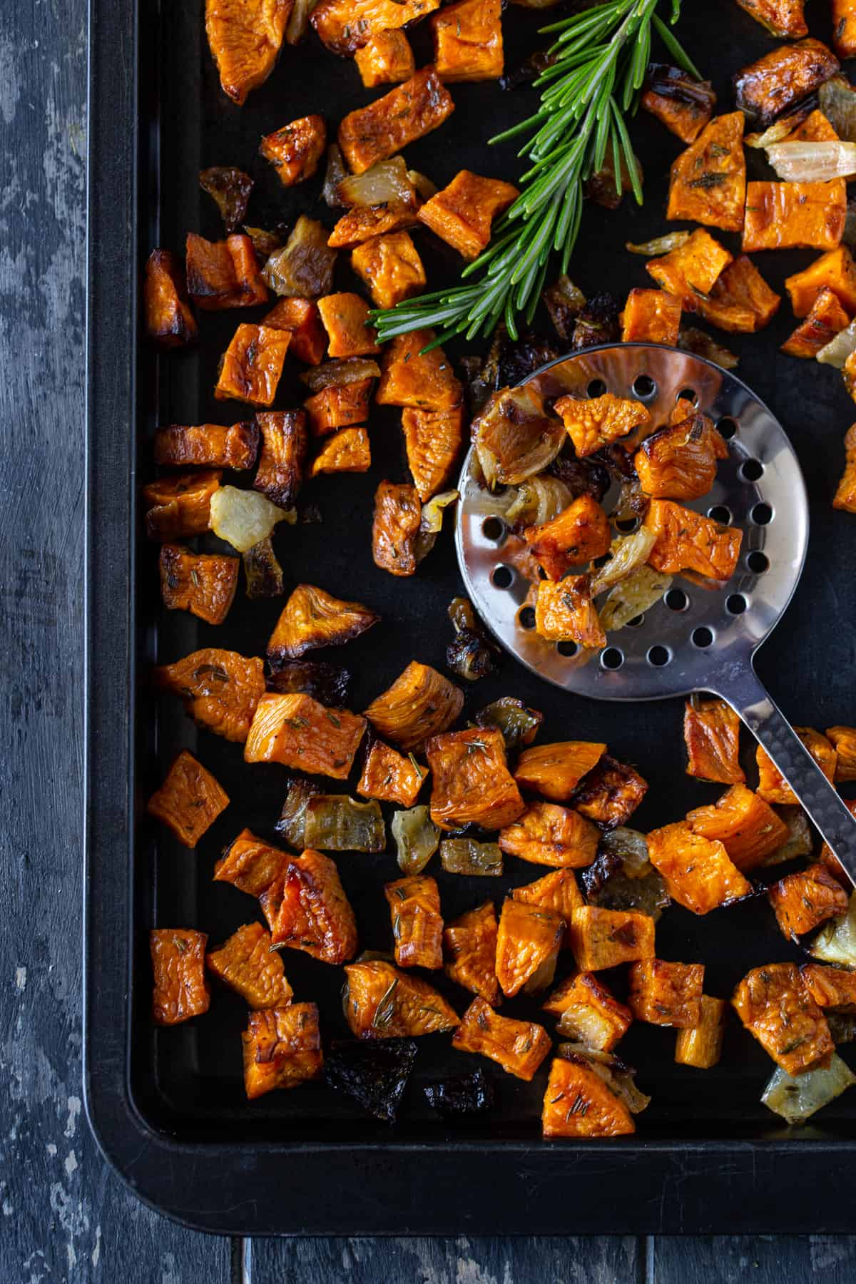 Dark sheet pan filled with roasted sweet potatoes and onions. Silver spoon lifting potatoes from pan.