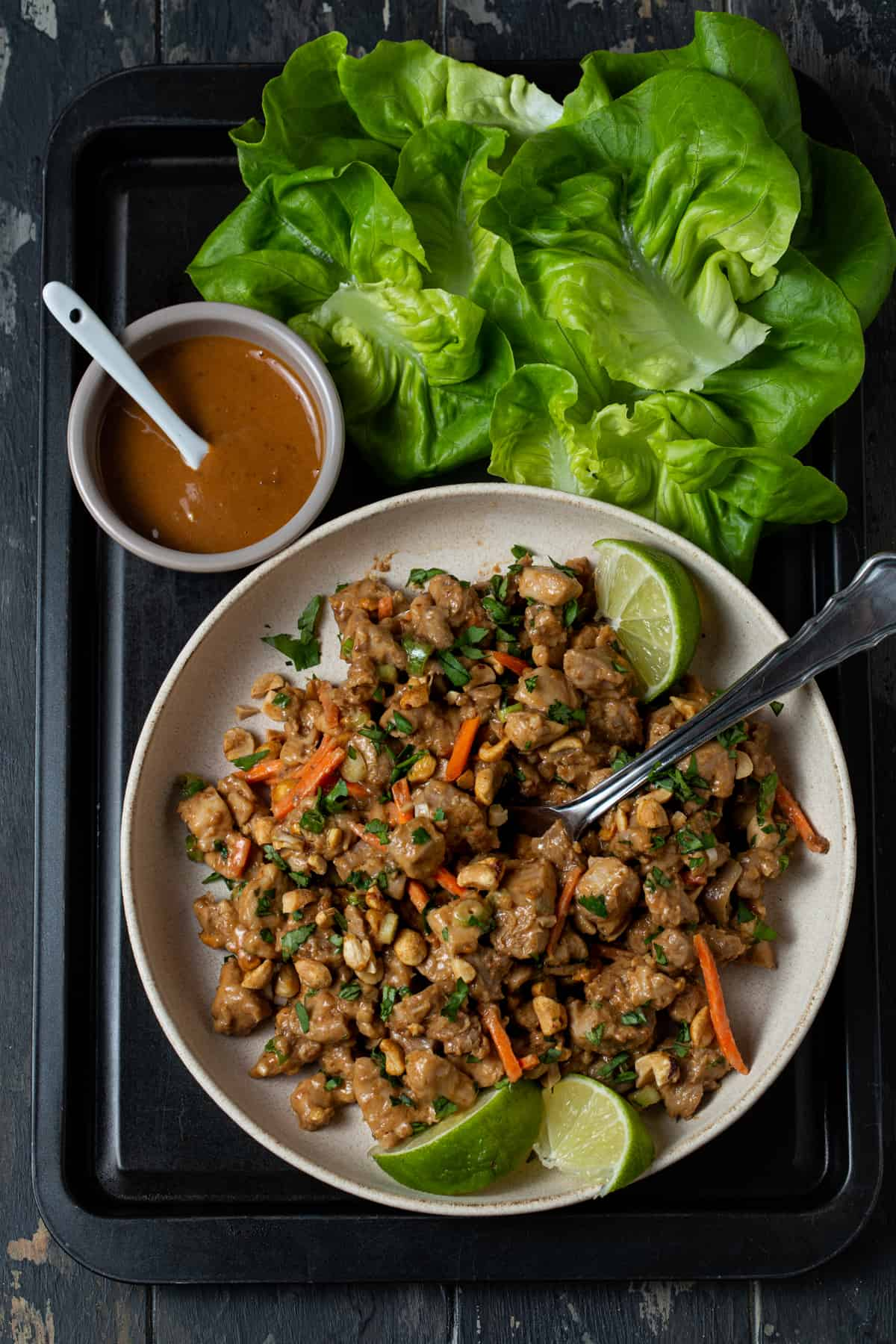 chopped chicken filling for lettuce wraps , bowl of peanut sauce and lettuce cups on black tray.