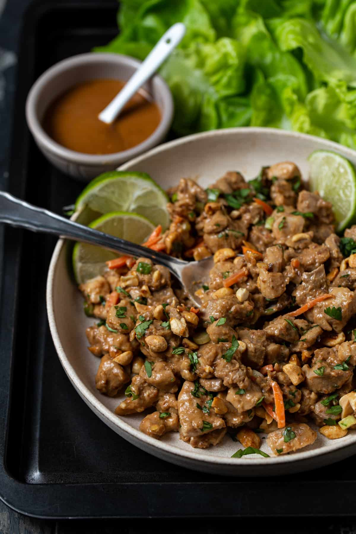 chopped chicken, cilantro carrots and peanuts in a peanut sauce on a gray plate.