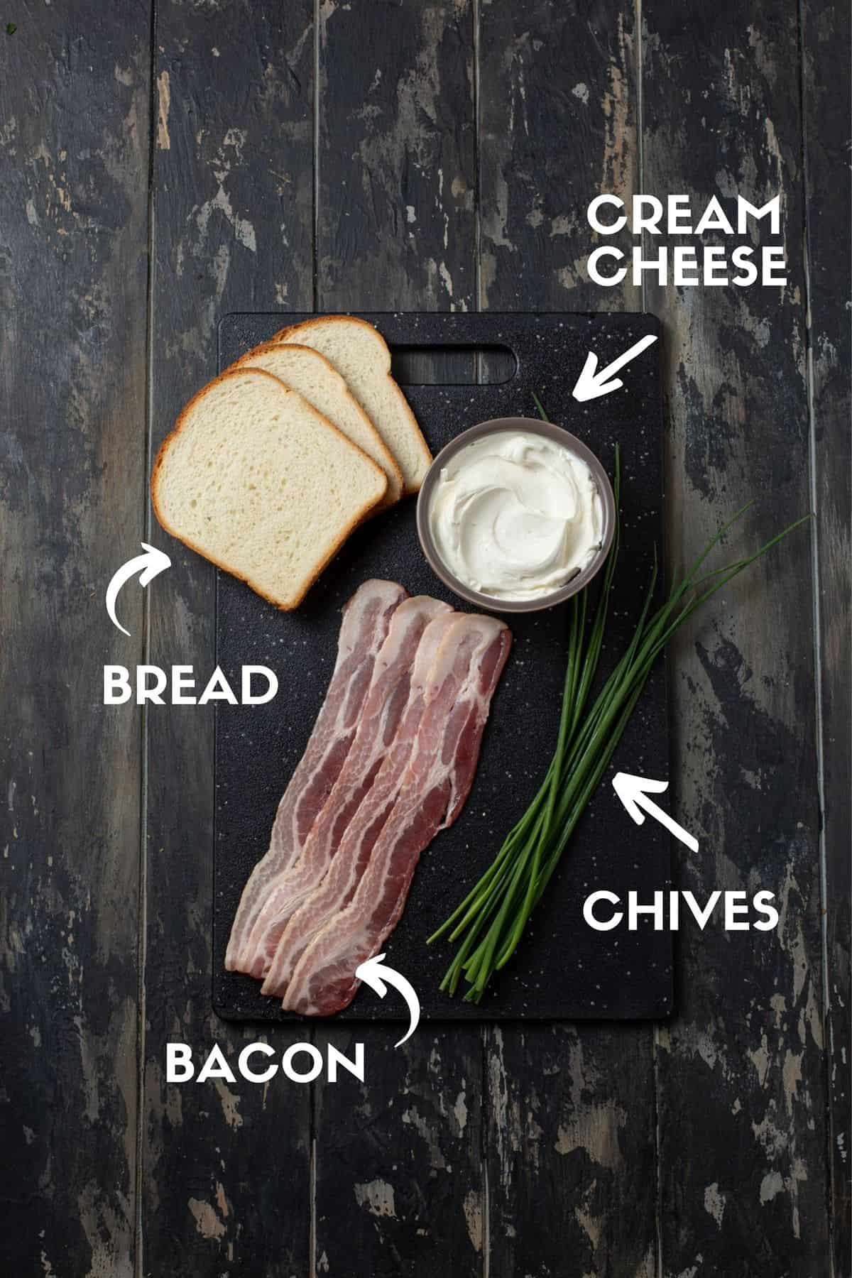 Bacon, chives, cream cheese and bread on a black board.