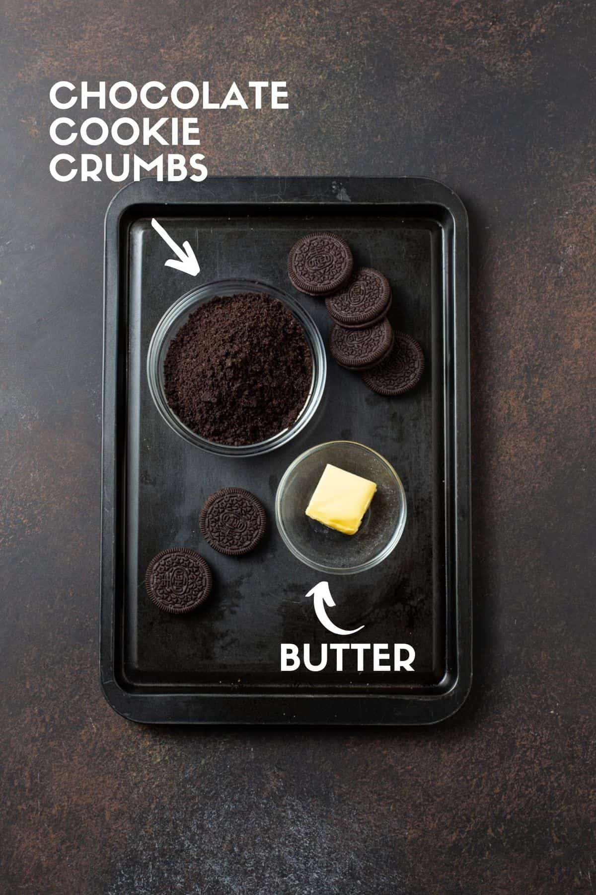 Dark sheet pan with chocolate cookies, bowl of cookie crumbs and butter.