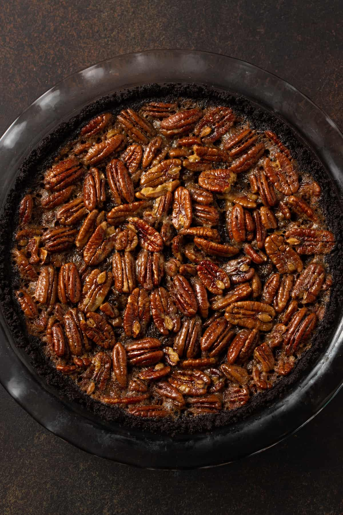 whole pecan pie in a glass pie plate on a brown background