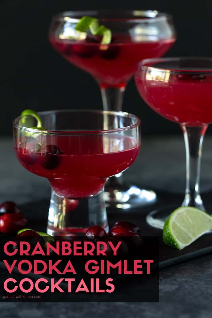 Cranberry gimlets in coupe glasses, with fresh cranberries and lime twists.