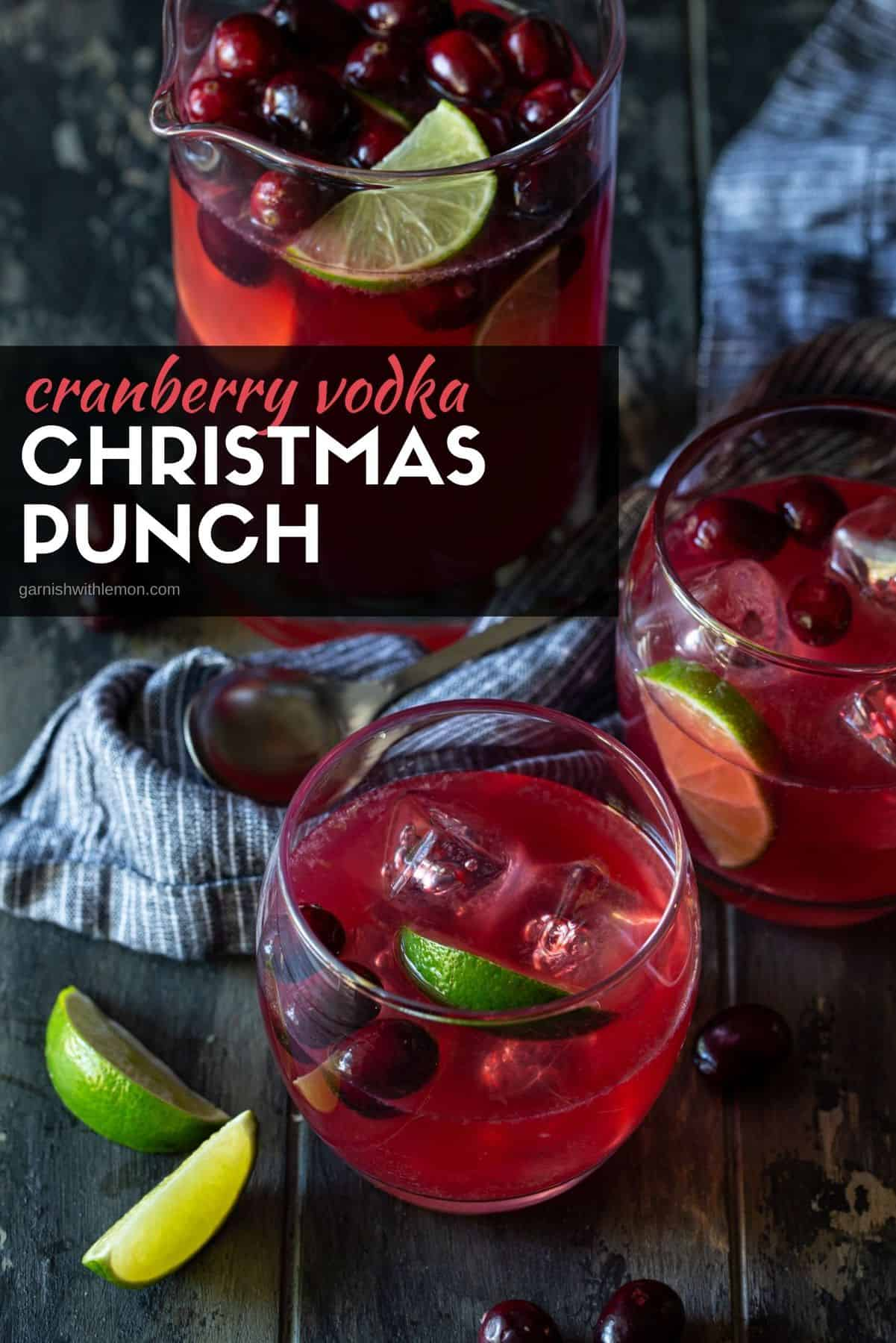 Two glasses of punch garrnished with fresh cranberries and lime wedges with a pitcher of punch in the background.