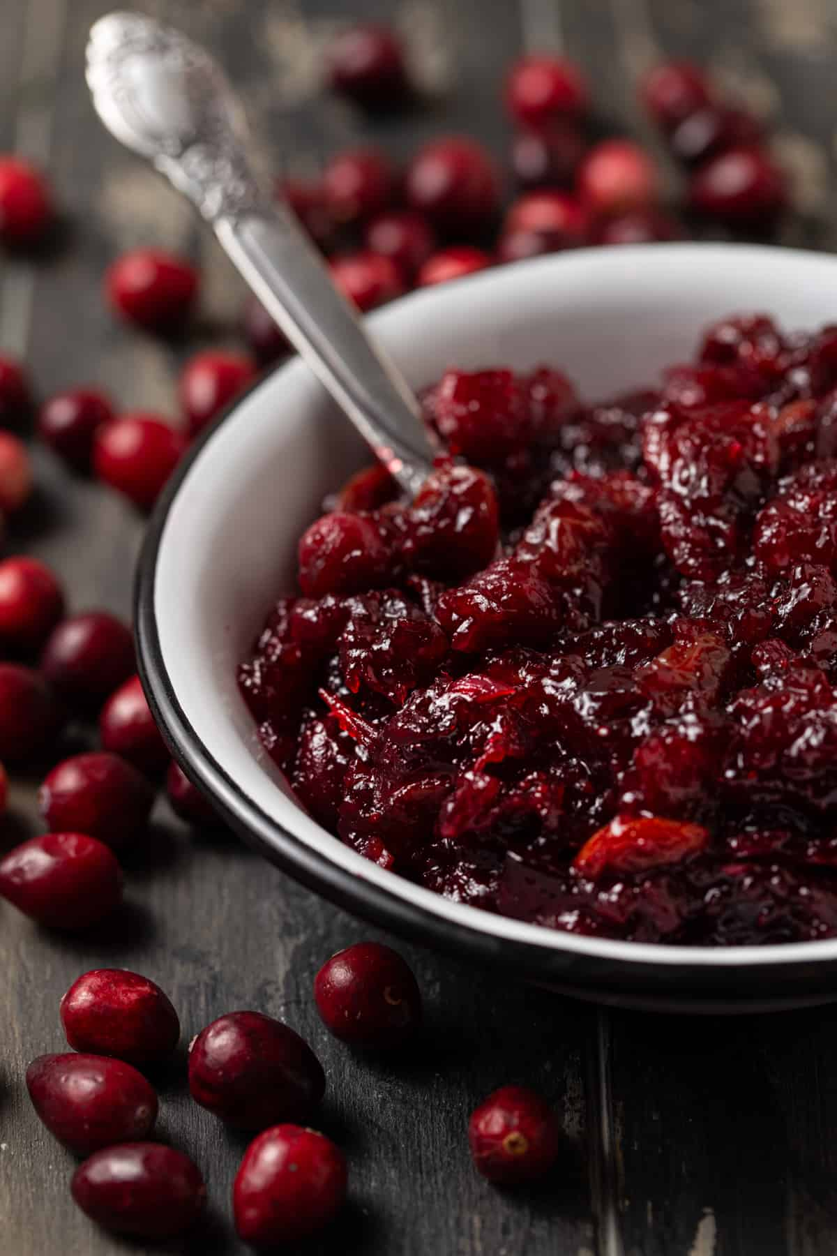 three quarter angle of cranberry sauce in white bowl on a dark wood board.