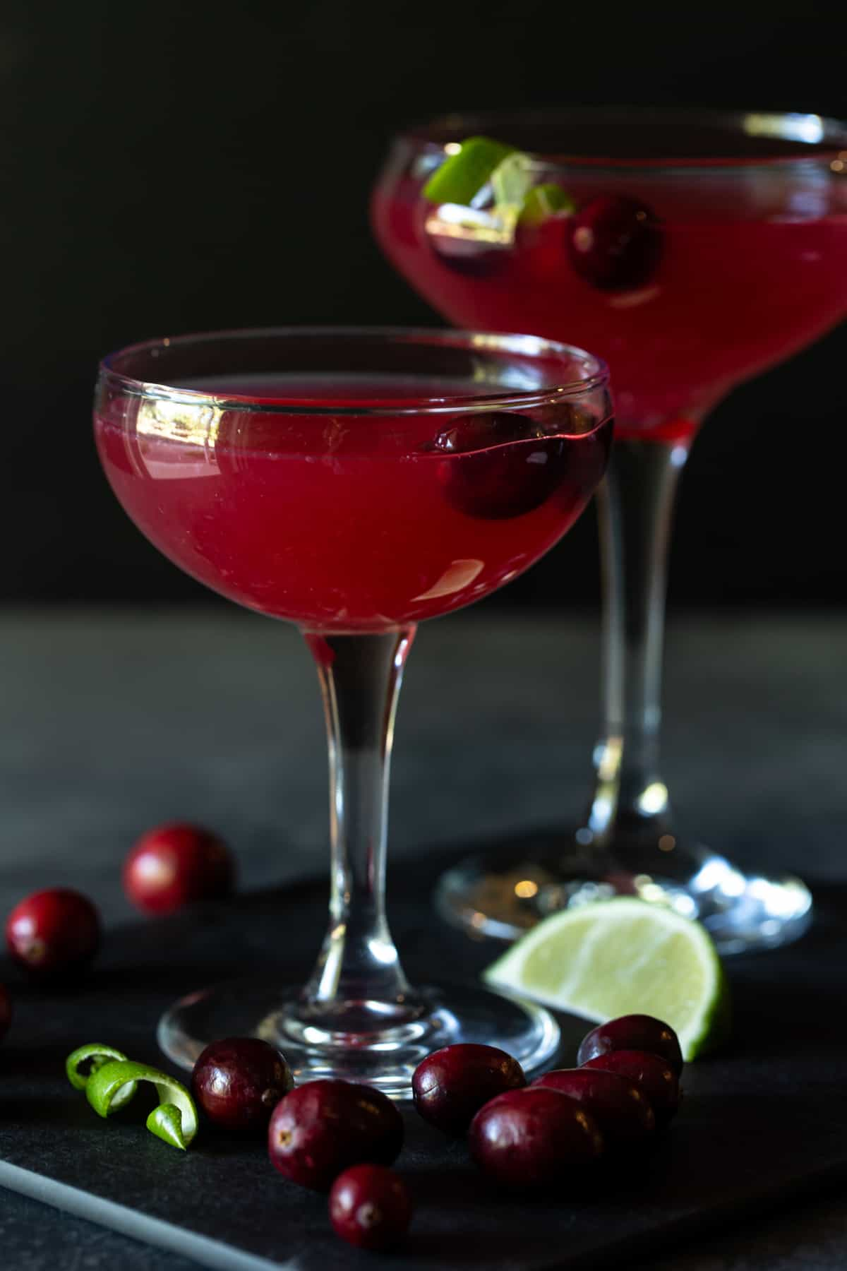 Two coupe glasses filled with cranberry gimlet drinks. Garnished with fresh cranberries and lime wedges.