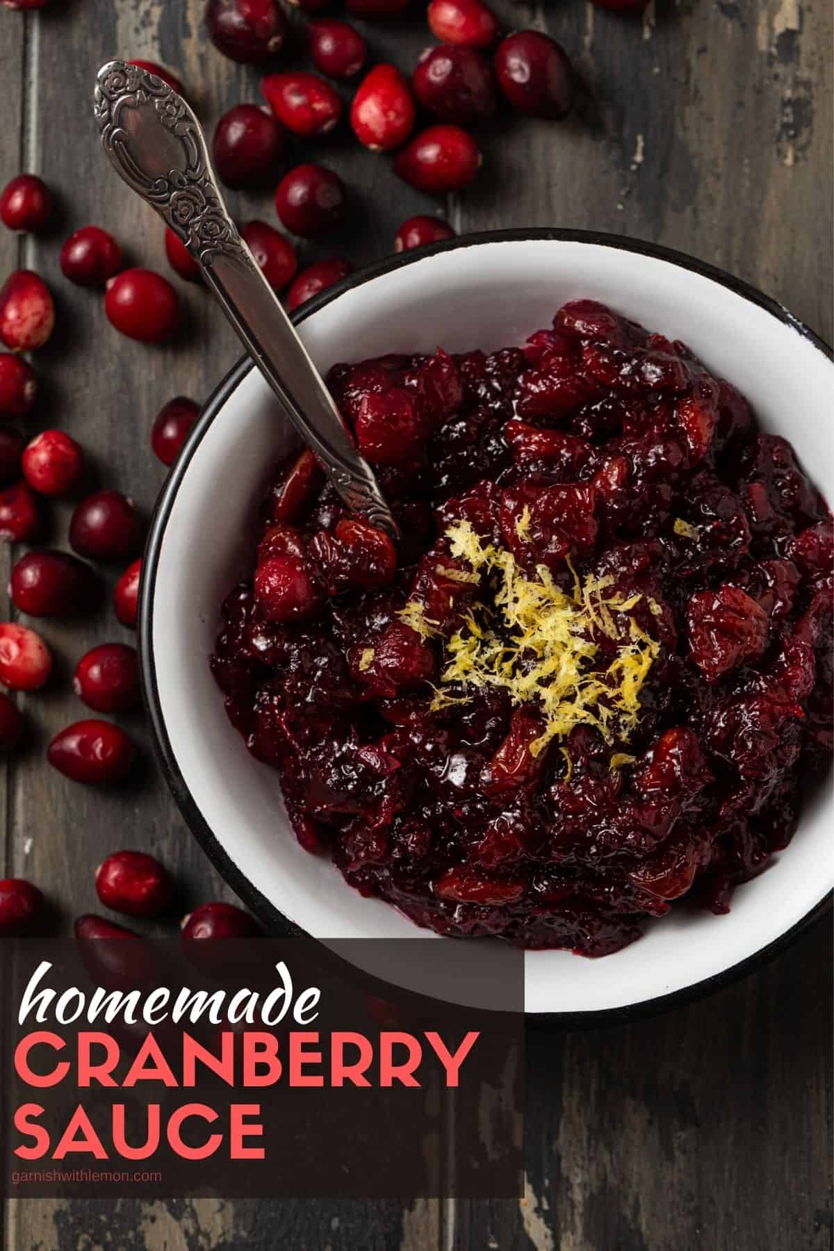 White bowl filled with cranberry sauce. Spoon inside bowl. Lemon zest topping on sauce.