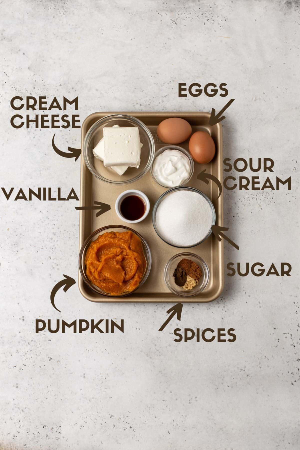 Ingredients for pumpkin cheesecake pie including pumpkin puree, sugar, cream cheese, eggs, spices & sour cream.