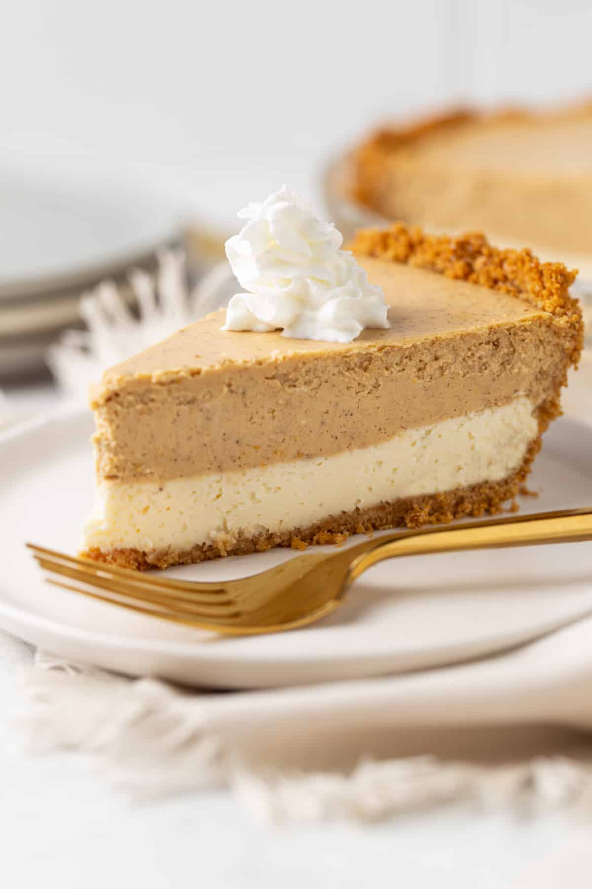 Piece of pie on a white plate with a gold fork.