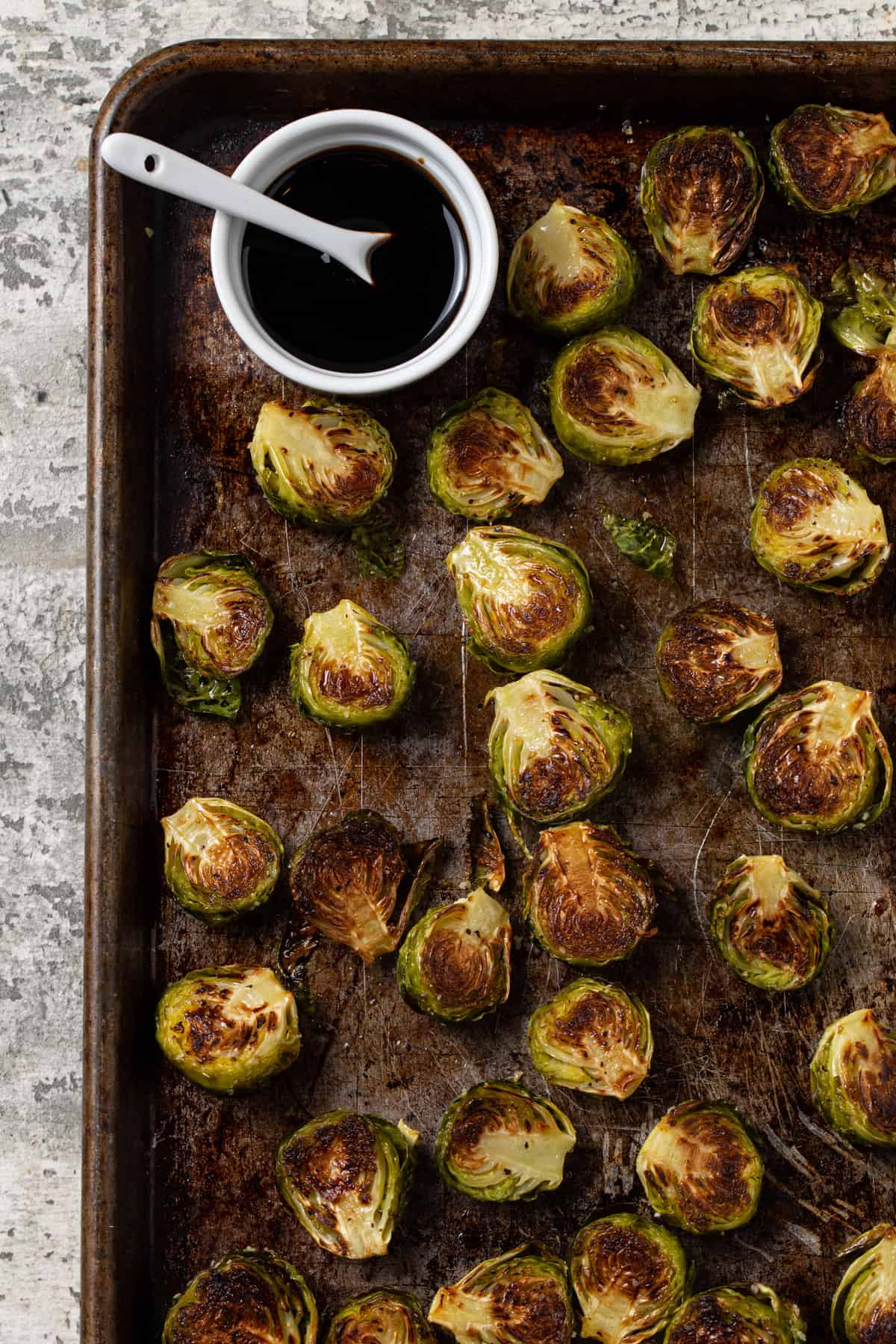 Large sheet pan with roasted brussels sprouts with small white bowl filled with balsamic reduction