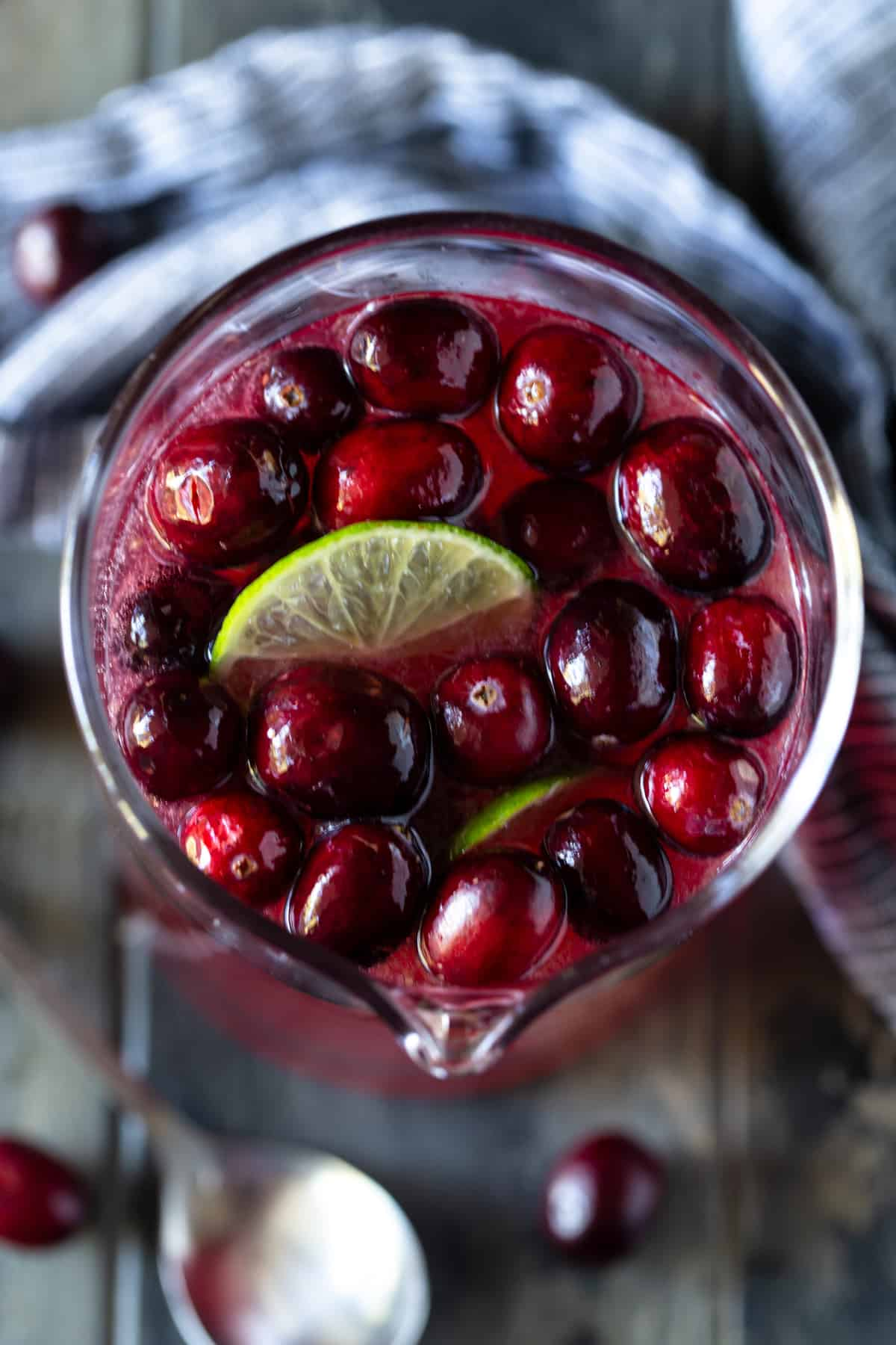 Cranberries and lime wedges floating on the top of punch in a pitcher.