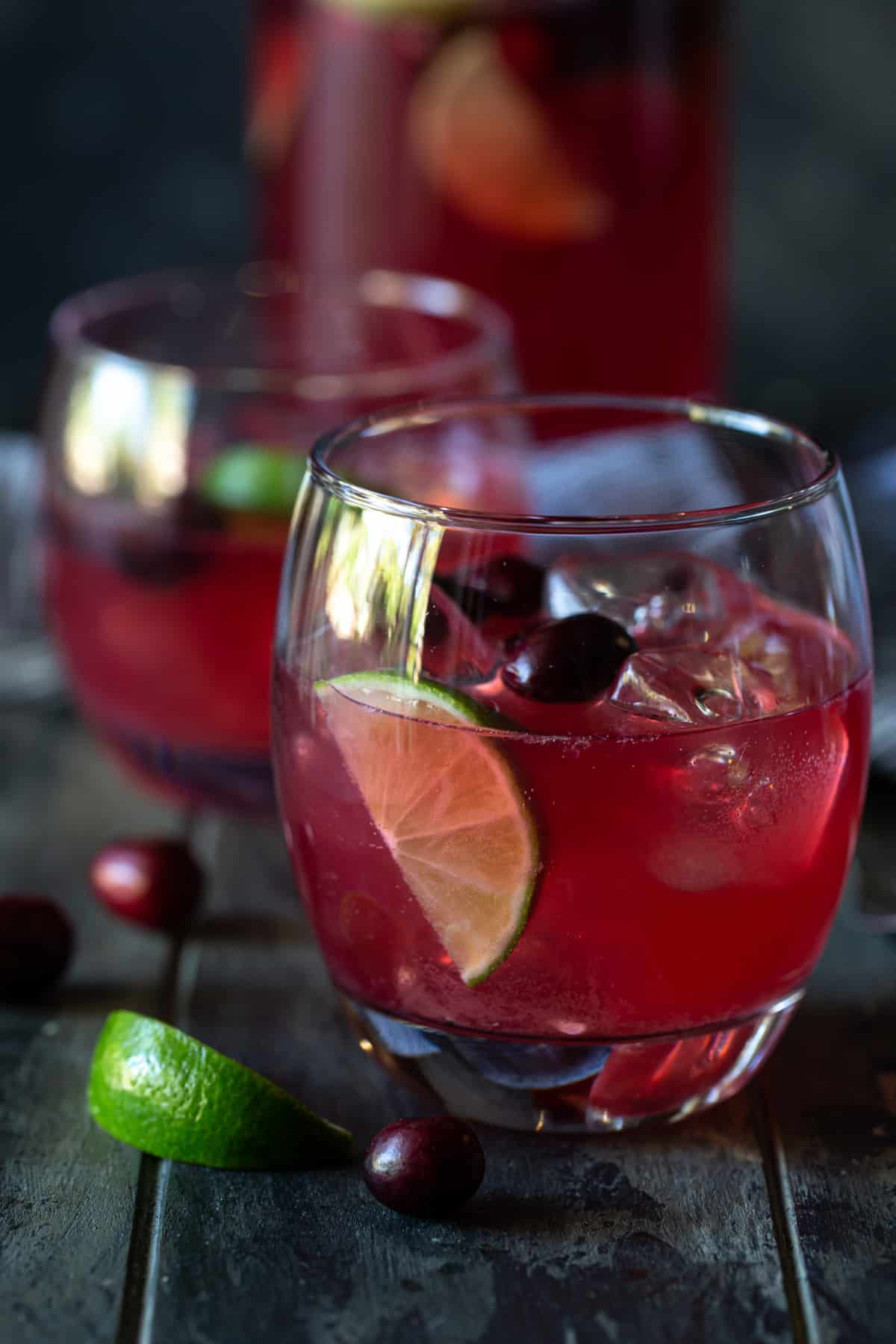 two glasses of punch in ice-filled glasses with lime wedges and fresh cranberries
