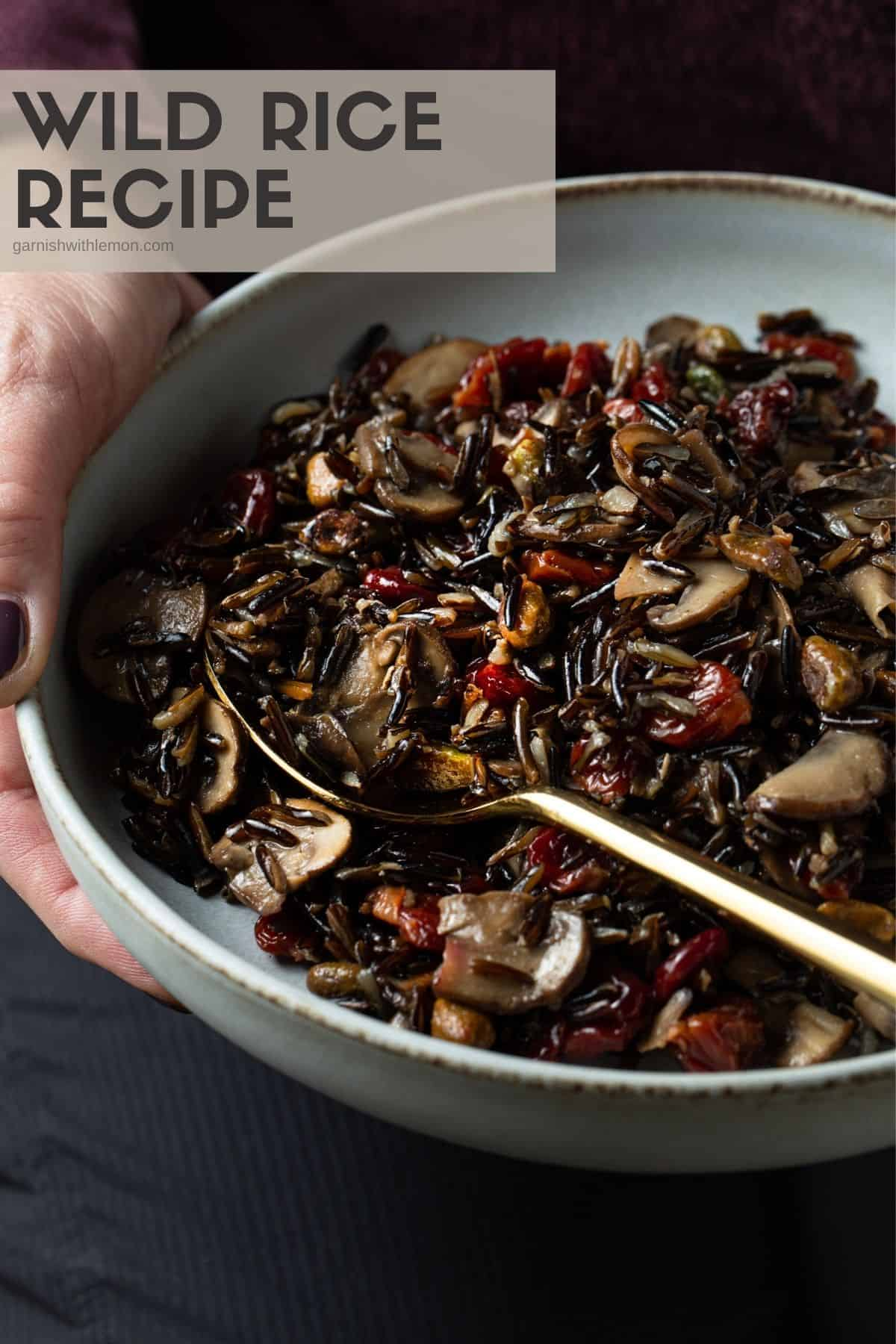 Cooked wild rice, pistachios, cherries and mushrooms in a gray bowl.